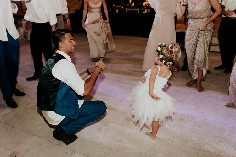 groom and flower girl dancing at reception