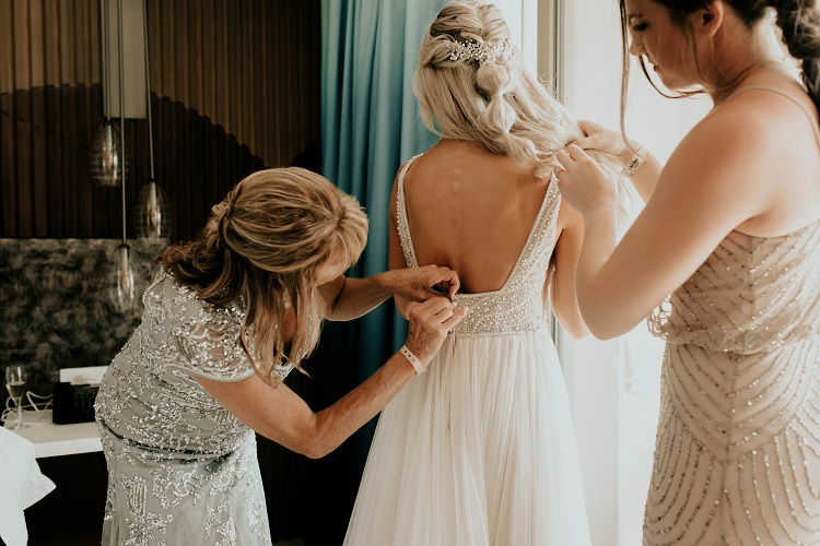 mother helping bride with wedding dress